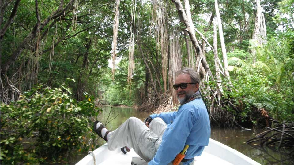 Guy seated on bow of boat heading through Jungle Waterways